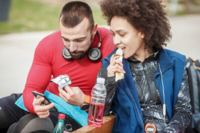 Young man and woman enjoying a protein bar during sports break